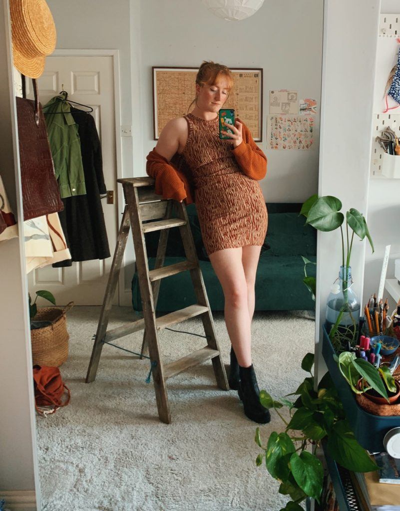 A front view of Roisin in her finished Axis tank dress, styled with a cardigan loosely worn. Roisin is resting an arm on the top of a step ladder which is to the side of her.